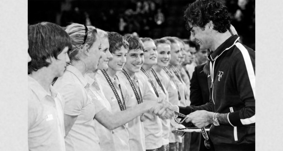 Roger Federer und die 12 Balljungen und -mädchen.